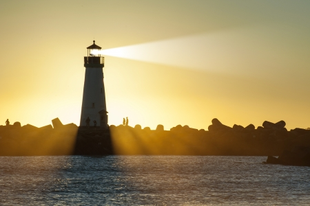 Lighthouse with light beam on ocean photo