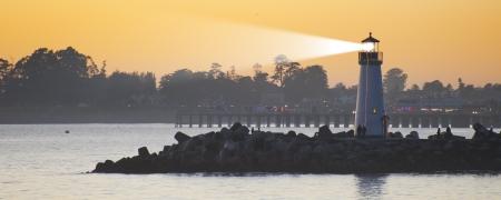 Lighthouse with light beam on ocean photo