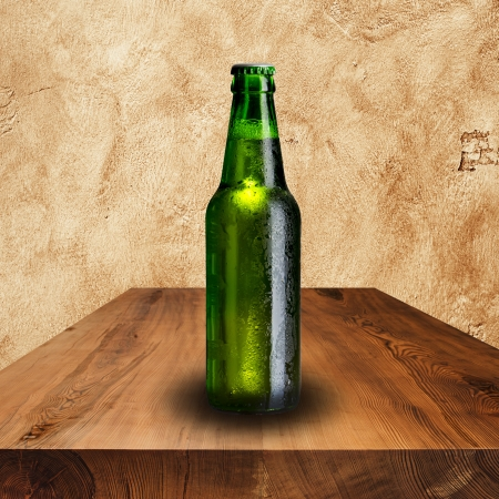 Bottle of beer on wood table with grunge background photo