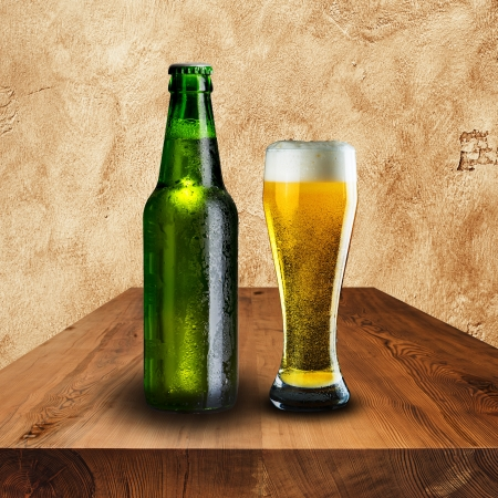 Bottle and glass of beer on wood table with grunge background photo