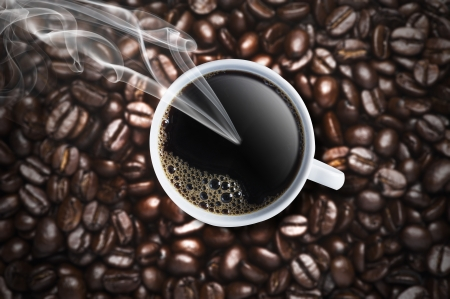 Cup of hot coffee with smoke on the coffee beans background