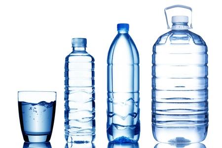 Glas water met verschillende maten flessen water