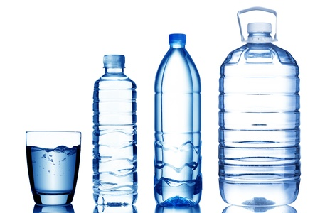 falling water: Glass of water with various sizes of water bottles Stock Photo
