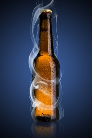 Smoke coming out from cold beer bottle on blue background photo