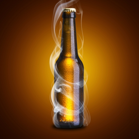 Smoke coming out from cold beer bottle on brown background photo