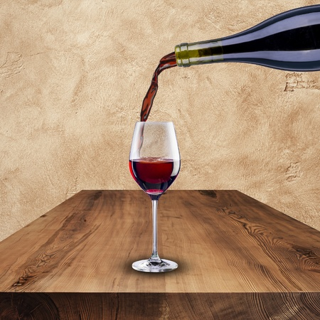 red wine pouring: Bottle of red wine pouring into glass