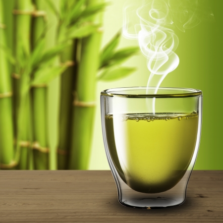 Glass of green tea on wood table with bamboo background photo