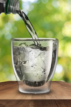 Water pouring into glass of water with ice