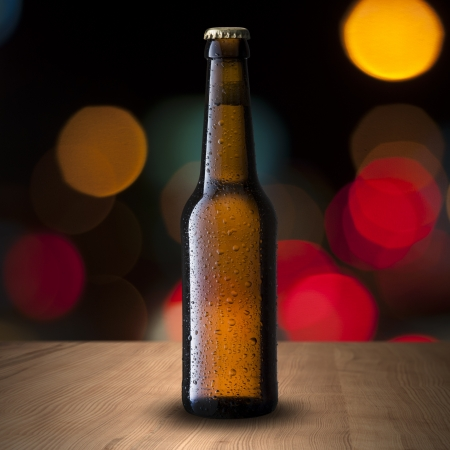 brewery: Beer Bottle on wood table with night scene background