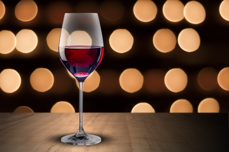 Glass of red wine on wood table and night scene background photo
