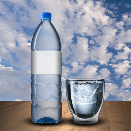 Glass and bottle of water on wood table photo