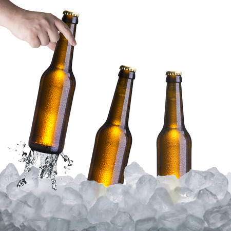 Hand holding beer bottle from ice cubes photo