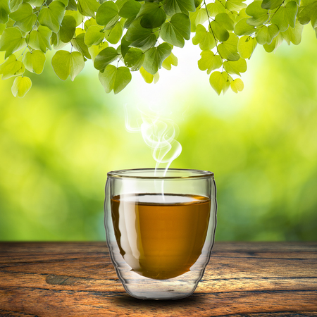 Hot tea on wood table and summer scene background photo