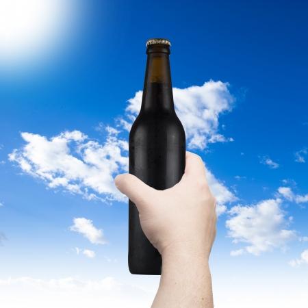Hand holding beer bottle photo