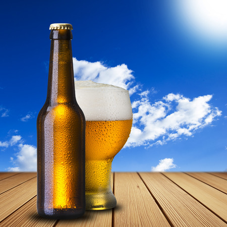 Beer on wood table with summer scene background photo