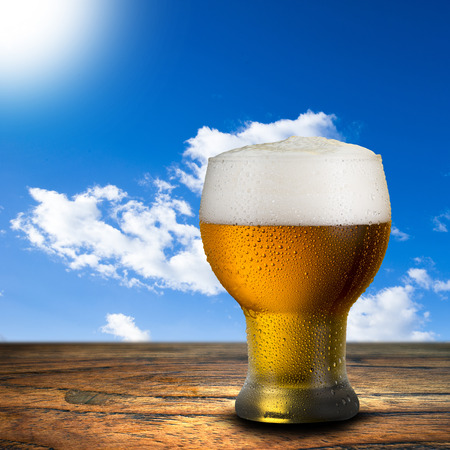 Glass of beer on wood table with summer scene background photo