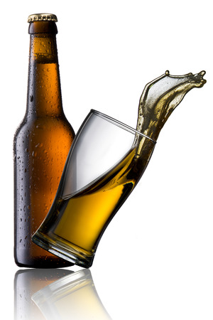 Beer splash from glass with cold beer bottle photo