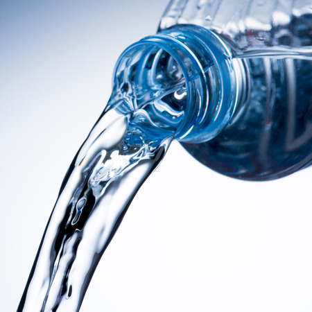 Pouring water from bottle Imagens