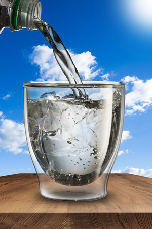 water pour into glass with ice cubes