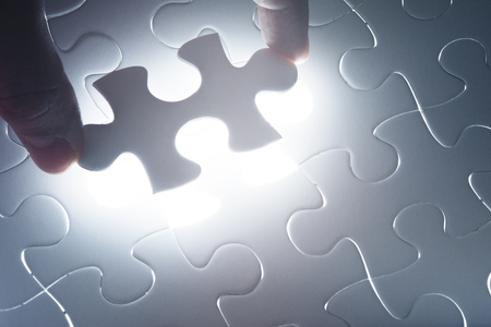 Missing jigsaw puzzle piece with light glow, business concept for completing the final puzzle piece photo