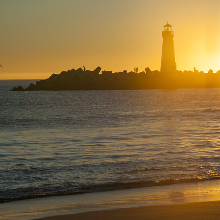 illuminative: Lighthouse at the Beach Stock Photo