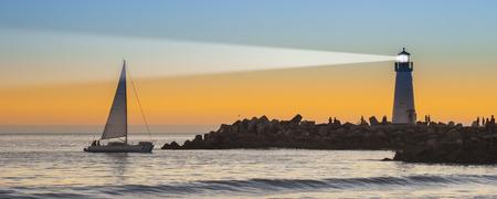 illuminative: Lighthouse with light beam at sunset