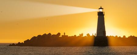 lighthouse with beam: Lighthouse with light beam at sunset