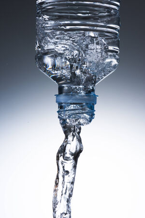 falling water: Water Pour from Water Bottle To Glass Stock Photo
