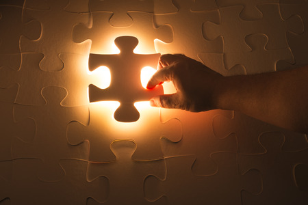 final piece of puzzle: Missing jigsaw puzzle piece with light glow, business concept for completing the final puzzle piece