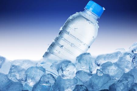 Koud Water Fles In Ice Cubes Stockfoto