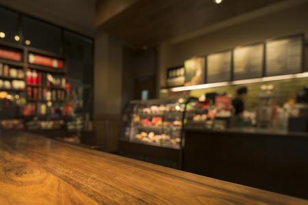 バック グラウンドでコーヒー ショップを望む木のテーブル