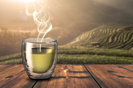 Hot Cup of Tea On Wood Table With Beautiful Sunrise Scene in Background Stock Photo