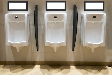 white urinals in mens bathroom, design of white ceramic urinals for men in luxuly toilet room with advertisement from on the top. Stock Photo