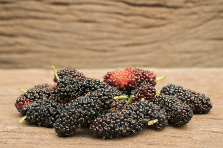 Mulberry berry on wood background macro photography,Food for heathly concept. Stock Photo