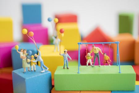 Miniatuur speelgoed. Gezin met ouders spelen op multi color houtblok. Familie concept.