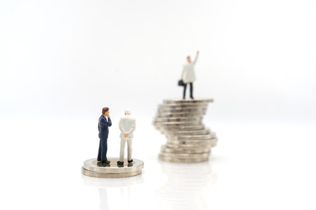 Miniature toy: Business man discussing about business on stack of coin and one man thinking how to success like that man, business ,financial, Success, Business Growth concept.