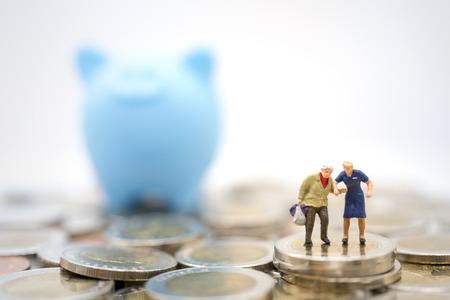 Miniaturowa zabawka: stary człowiek robi zakupy lub podróżuje po przejściu na emeryturę na stosie monet i skarbonce. Oszczędność pieniędzy po przejściu na emeryturę, biznes, zakupy, koncepcja podróży