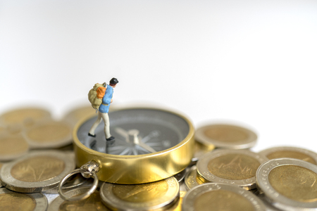 Miniature toy:Young hipster tourist planning saving money for tour on compass and coins : tour ,saving money ,adventure concept.