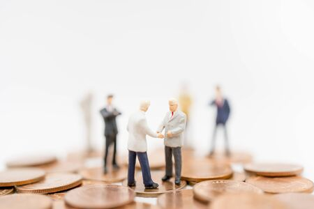 Miniature toy: Business man discussing about business on stack of coin , business ,financial, Success, Business Growth concept. Stock Photo
