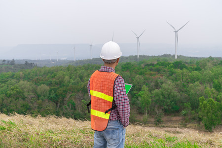 Success engineer man with safety helmet looking to tablet for check condition of wind turbine on the high hill mountain.On hand holding tablet .Wind turbine electric generator,clean energy concept. Archivio Fotografico