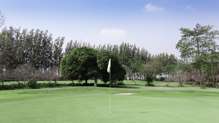 Beautiful tropical golf course ,green for putt and yellow flag.Healthy exercise golf game concept. Standard-Bild