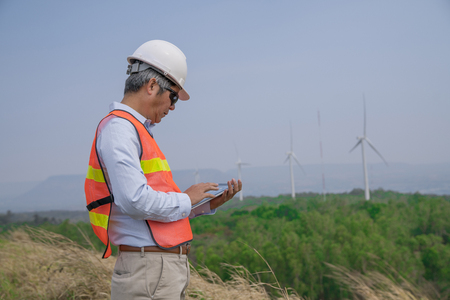 Senior Asian engineer man with safety helmet talking abount working and holding tablet for checking condition of wind turbine on the high hill mountain.Wind turbine electric generator,clean energy concept.