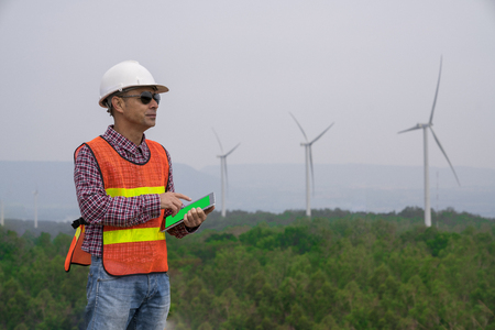 Success engineer man with safety helmet looking to wind turbine for checking its working on the high hill mountain.On hand holding tablet .Wind turbine electric generator,clean energy concept.