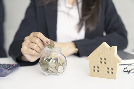 business woman saving for buy house.put coin to glass cup and calculate money. Archivio Fotografico