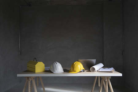 Yellow and white safety helmet ,yellow tool box and blue pritn home drawing on wood table.Architecture or civil engineer concept. Archivio Fotografico