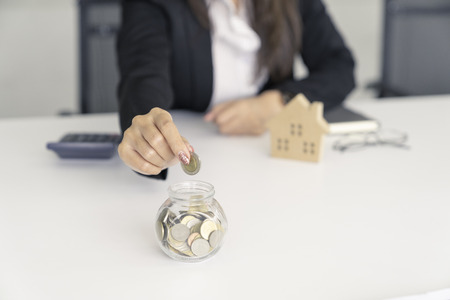 business woman saving for buy house.put coin to glass cup and calculate money. Archivio Fotografico - 109471513