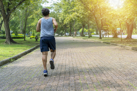 Sporty man jogging or exercise in national park on early morning .Sport concept. Archivio Fotografico - 109634642