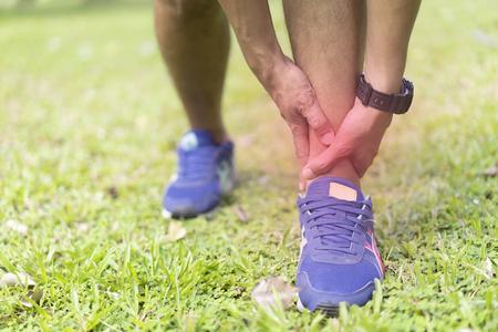 sportif tenant sa douleur à la cheville en faisant du jogging ou en courant dans le parc national. Banque d'images