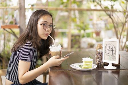 Beautiful young woman used mobile in coffee shop. Archivio Fotografico - 109648268
