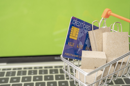 Selling or buying online,shopping online or e-commerce with paper box ,paper bag and credit card in shopping cart or trolley. Archivio Fotografico - 111266266